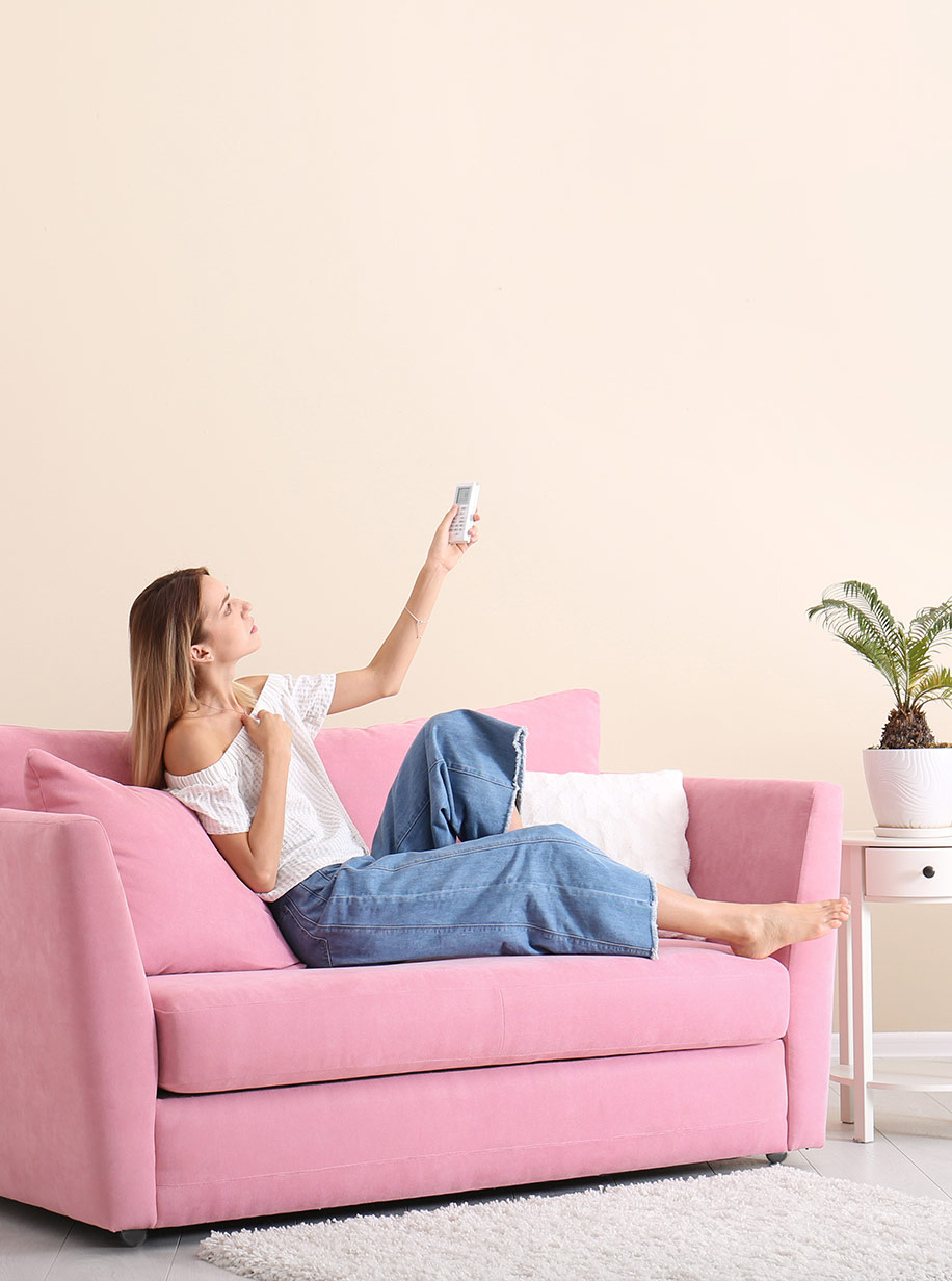 A lady on a pink couch turning on split system airconditioning.