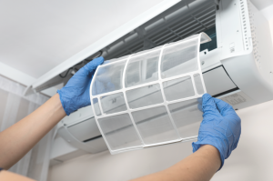 A person cleaning an air conditioning filter with gloves on.
