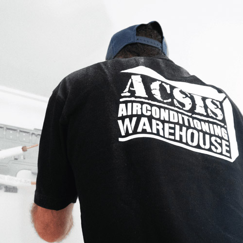 A staff member at leading Airconditioning supplier and installer; Acsis Airconditioning warehouse installing a brand new Daikin unit.