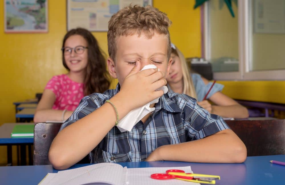 Student with cold covering his nose and mouth.