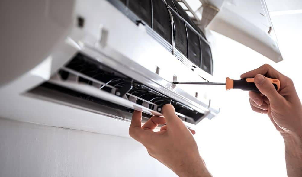 Removing screw from aircon using screwdriver.