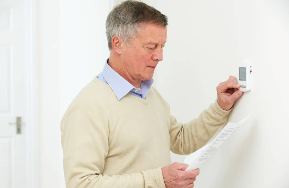 Man checking power bill while adjusting thermostat.