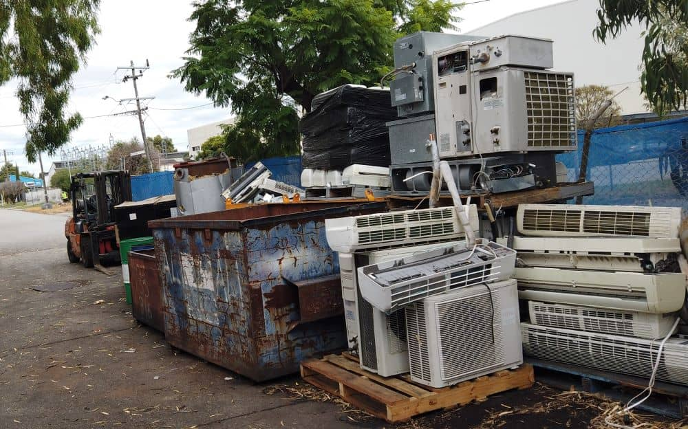 Pile of disposed air conditioners in a scrap yard.