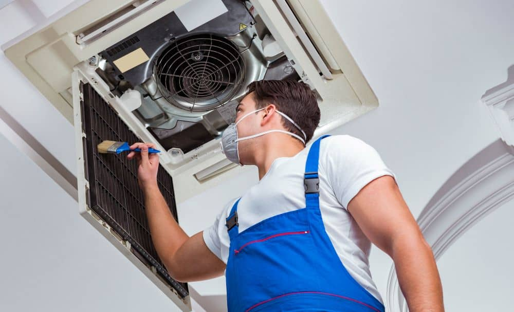 Worker cleaning air conditioner filter.